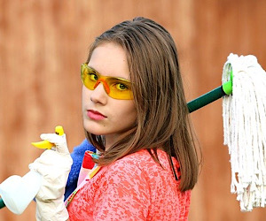 girl holding mop and spray bottle